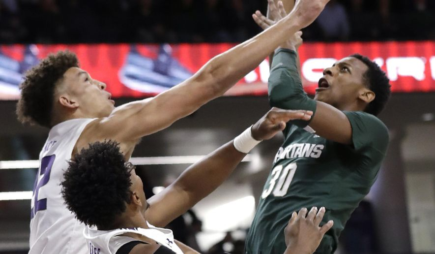 Michigan State forward Marcus Bingham Jr., right, shoots against Northwestern guard Pat Spencer, left, and guard Anthony Gaines during the first half of an NCAA college basketball game Wednesday, Dec. 18, 2019, in Evanston, Ill. (AP Photo/Nam Y. Huh)