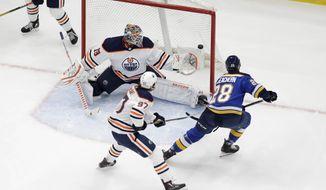 St. Louis Blues' Mackenzie MacEachern (28) scores past Edmonton Oilers goaltender Mikko Koskinen (19), of Finland, and Connor McDavid (97) during the third period of an NHL hockey game Wednesday, Dec. 18, 2019, in St. Louis. The Blues won 2-1. (AP Photo/Jeff Roberson)