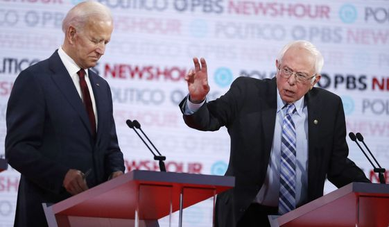 Democratic presidential candidate Sen. Bernie Sanders, I-Vt., right, speaks as former Vice President Joe Biden listens during a Democratic presidential primary debate Thursday, Dec. 19, 2019, in Los Angeles. (AP Photo/Chris Carlson)