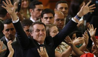 Brazil's President Jair Bolsonaro waves tot he crowd during a Christmas celebration with staff and students at the Planalto Presidential Palace, in Brasilia, Brazil, Thursday, Dec. 19, 2019. (AP Photo /Eraldo Peres)