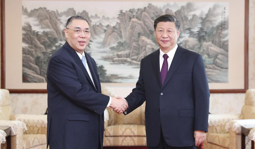In this photo released by Xinhua News Agency, Chinese President Xi Jinping, at right shakes hands with outgoing Macao Chief Executive Fernando Chui Sai-on in Macao on Wednesday, Dec. 18, 2019. Xi will attend the 20th anniversary celebrations of Macao's return to China. (Wang Ye/Xinhua via AP)