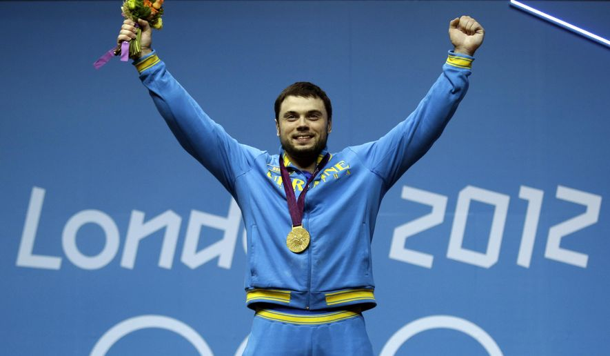 FILE - In this Monday, Aug. 6, 2012 file photo, gold medalist Oleksiy Torokhtiy of Ukraine participates in the medal presentation after the men's 105-kg weightlifting competition at the 2012 Summer Olympics in London. Ukrainian weightlifter Oleksiy Torokhtiy has been stripped of the gold medal he won at the 2012 Olympics and banned for doping.(AP Photo/Ng Han Guan, File)