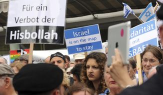 "FILE---Picture taken on July 2, 2019 shows people taking part in a demonstration under the alliance  ""No Al Quds march 2016! Together against all anti-Semitism!"") at Kurfuerstendamm in Berlin, Germany. Banner left reads ""ban Hezbollah"". (Wolfgang Kumm/dpa via AP)"