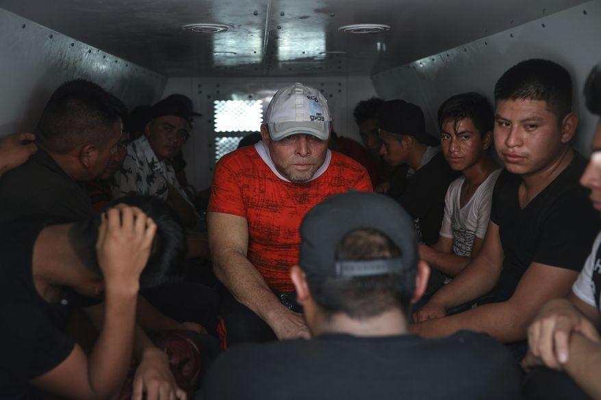 In this Nov. 26, 2019, file photo, migrants are held in a van of the National Migration Institute after they were found in the cargo hold of a truck where dozens of Central American migrants were being smuggled, at an immigration checkpoint in Medellin de Bravo, Veracruz state, Mexico. Except for official border crossings, nearly every mile of river, desert and mountain along the U.S.-Mexican border is under the control of Mexico's organized crime rings, which decide who can cross and how much they will pay. (AP Photo/Felix Marquez) ** FILE **
