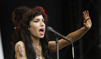 """FILE - In this Aug. 17, 2008 file photo, British singer Amy Winehouse performs at the V Festival in Chelmsford, Essex. The first-ever Amy Winehouse exhibit in the U.S. will debut at the Grammy Museum in Los Angeles next month. The Recording Academy told The Associated Press on Thursday, Dec. 19, 2019, that the late British singer's popular outfits - including her halter dress worn at her final stage performance in Belgrade in 2011 - never-before-seen handwritten lyrics and home video, journal entries and more from her family's personal archive will make up """"Beyond Black - The Style of Amy Winehouse."""" The exhibit opens on Jan. 17, 2020 and will run through April 13. (AP Photo/Joel Ryan, File)"""