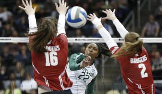 Baylor's Yossiana Prerssley (22) spikes the ball between Wisconsin's Dana Tettke (16) and Sydney Hilley (2) during a semifinal game of the NCAA Div I Women's Volleyball Championships, Thursday, Dec. 19, 2019, in Pittsburgh. (AP Photo/Keith Srakocic)