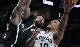 San Antonio Spurs' DeMar DeRozan (10) shoots as Brooklyn Nets' Taurean Prince, left, and Wilson Chandler defend during the first half of an NBA basketball game Thursday, Dec. 19, 2019, in San Antonio. (AP Photo/Darren Abate)