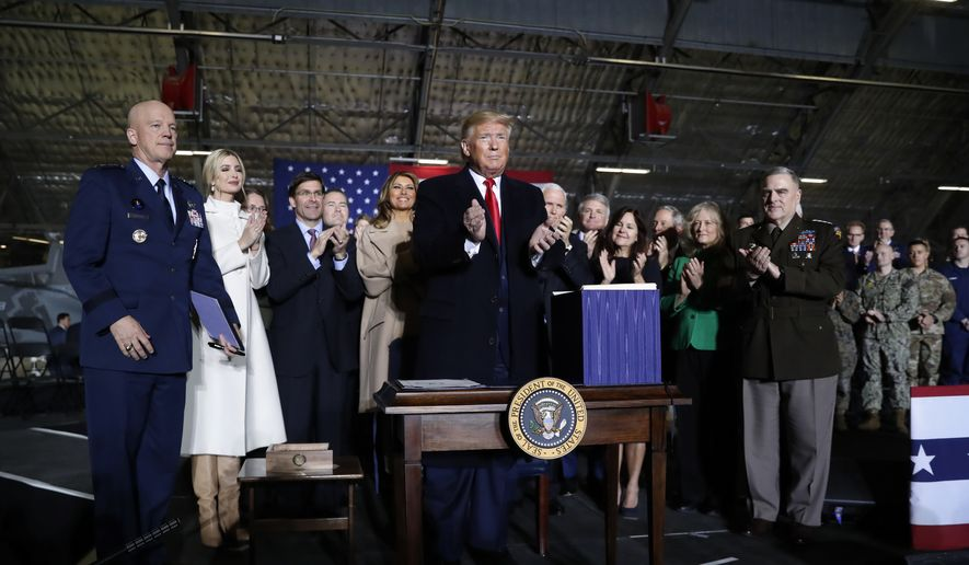 President Donald Trump applauds after signing the National Defense Authorization Act for Fiscal Year 2020 at Andrews Air Force Base, Md., Friday, Dec. 20, 2019, before traveling to Mar-a-lago in Palm Beach, Fla. (AP Photo/Andrew Harnik)