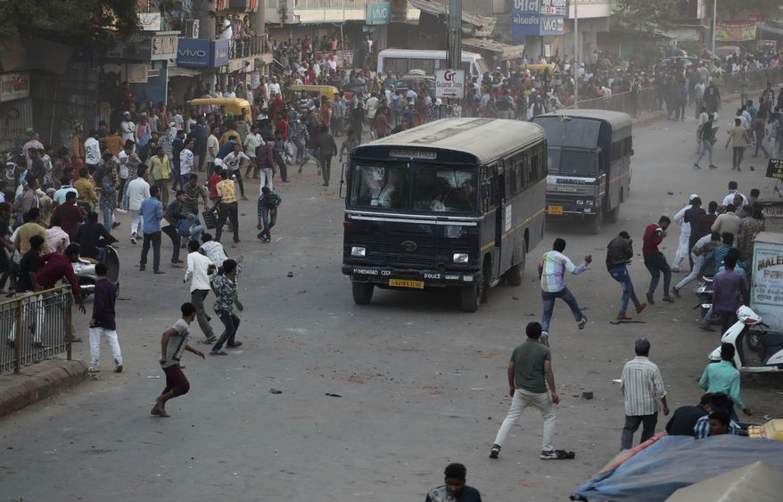 Indians throw stones on police vehicles during a protest against the Citizenship Amendment Act and the National Register of Citizens in Ahmadabad, India, Thursday, Dec. 19, 2019. Police detained several hundred protesters in some of India's biggest cities Thursday as they defied a ban on assembly that authorities imposed to stop widespread demonstrations against a new citizenship law that opponents say threatens the country's secular democracy. (AP Photo/Ajit Solanki)