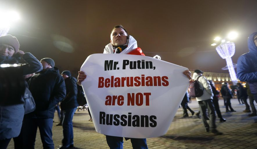 A Belarusian demonstrator holds a poster as other gather to protest closer integration with Russia which protesters fear could erode the post-Soviet independence of Belarus, in downtown in Minsk, Belarus, Friday, Dec. 20, 2019. The presidents of Belarus and Russia have met to discuss deeper economic ties between the two close allies amid mounting concerns in Minsk that Moscow ultimately wants to subdue its neighbor.(AP Photo/Sergei Grits)