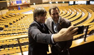 Catalonia's former regional president Carles Puigdemont, left, and former Catalan regional minister Antoni Comin take a selfie overlooking the plenary chamber at the European Parliament in Brussels, Friday, Dec. 20, 2019. In a potentially stinging reversal for Spanish justice authorities, the European Union's top court ruled that a former Catalan official serving a prison sentence for his role in a banned independence referendum two years ago had the right to parliamentary immunity when he was on trial. (AP Photo/Francisco Seco)