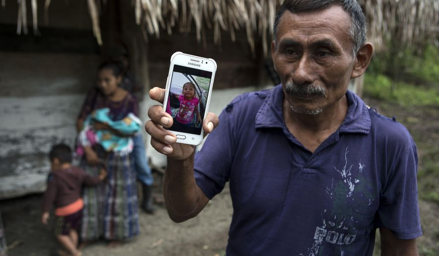 FILE - In this Dec. 15, 2018, file photo, Domingo Caal Chub, 61, holds a smartphone displaying a photo of his granddaughter, Jakelin Amei Rosmery Caal Maquin, in Raxruha, Guatemala. The 7-year-old girl died in a Texas hospital, two days after being taken into custody by border patrol agents in a remote stretch of New Mexico desert. Homeland Security's watchdog found no wrongdoing or misconduct by immigration officials in the deaths of the girl and another boy last December (AP Photo/Oliver de Ros, File)