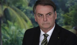 FILE - In this Oct. 1, 2019 file photo, President Jair Bolsonaro attends a ceremony to launch an agro program at the Planalto presidential palace in Brasilia, Brazil. Bolsonaro lashed out at journalists on Friday, Dec. 20 singling out one as looking like a homosexual, as news reports of a corruption investigation linked to his son continued making headlines. (AP Photo/Eraldo Peres, File)