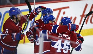 Montreal Canadiens' Max Domi (13) celebrates his overtime goal against the Calgary Flames during an NHL hockey game Thursday, Dec. 19, 2019, in Calgary, Alberta. (Jeff McIntosh/The Canadian Press via AP)