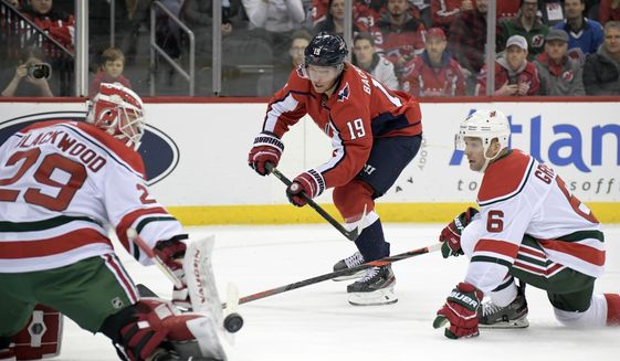 New Jersey Devils goaltender Mackenzie Blackwood (29) deflects a shot by Washington Capitals center Nicklas Backstrom (19) as Devils defenseman Andy Greene (6) also defends during the first period of an NHL hockey game Friday, Dec. 20, 2019, in Newark, N.J. (AP Photo/Bill Kostroun)
