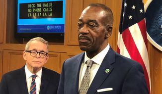 Jack Marchbanks, right, the Ohio Transportation Department director, reflects on the damage caused by distracted driving in the state, at a news conference promoting safe holiday driving and also attended by Ohio Gov. Mike DeWine, on Friday, Dec. 20, 2019, in Columbus, Ohio. DeWine said he wants distracted driving made a primary offense and promised a legislative proposal soon. (AP Photo/Andrew Welsh-Huggins)