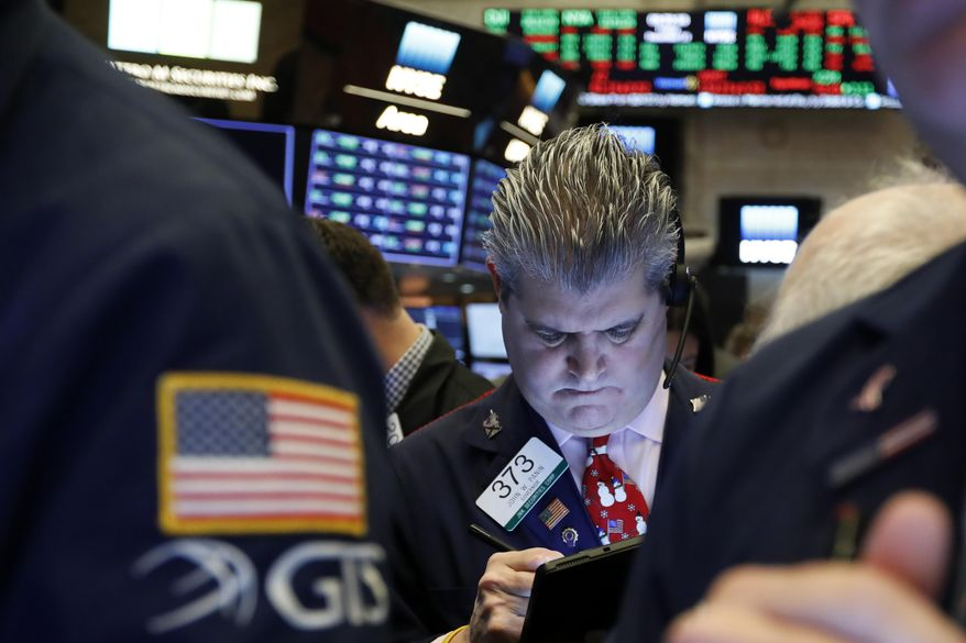 FILE - In this Dec. 13, 2019, file photo trader John Panin works on the floor of the New York Stock Exchange. The U.S. stock market opens at 9:30 a.m. EST on Friday, Dec. 20. (AP Photo/Richard Drew, File)