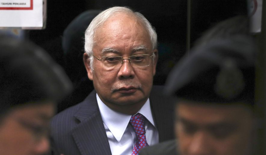 FILE - In this June 18, 2019, file photo, former Malaysian Prime Minister Najib Razak walks into the lift as he arrives at Kuala Lumpur High Court in Kuala Lumpur, Malaysia. Najib made a religious oath in a mosque Friday, Dec. 20, 2019, denying a new accusation that he ordered the killing of a Mongolian woman 13 years ago.(AP Photo/Vincent Thian, File)