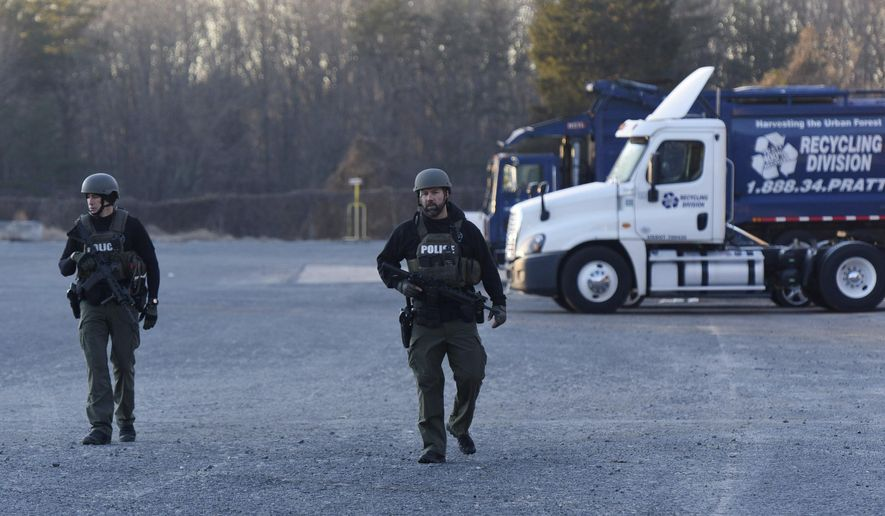 Winston-Salem Police officers in tactical gear patrol outside the  Joycelyn V. Johnson Municipal Services Center after reports of gunshots in Winston-Salem, N.C. early Friday, Dec. 20, 2019. Winston- Salem Police are confirming there was a shooting but are not saying at this time if there are any injuries or deaths. (Walt Unks/Winston-Salem Journal via AP)