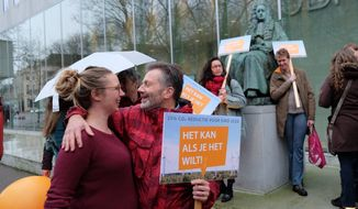 Climate activists gather outside the Supreme Court of the Netherlands, The Hague, on Friday Dec. 20, 2019, ahead of a ruling in a landmark case in which the government was ordered to slash greenhouse gas emissions by 25% by 2020. The government appealed saying that the ruling effectively meant that courts were setting government policy. (AP Photo/Mike Corder)