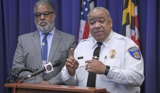 City solicitor Andre Davis, left, listens as Baltimore Police Commissioner Michael Harrison, right, announces support for a pilot program that uses surveillance planes over the city to combat crime on Friday, Dec. 20, 2019, in Baltimore. (Jerry Jackson/The Baltimore Sun via AP)