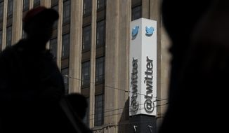 FILE - This July 9, 2019, file photo shows pedestrians walking across the street from the Twitter office building in San Francisco. Twitter says it has removed nearly 6,000 accounts it has deemed tied to a state-backed information operation in Saudi Arabia. (AP Photo/Jeff Chiu, File)