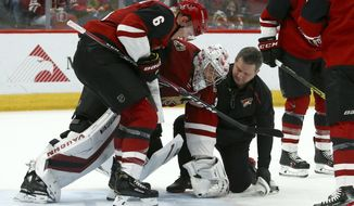 Arizona Coyotes goaltender Darcy Kuemper, middle, is helped off the ice by defenseman Jakob Chychrun (6) and head athletic trainer Dave Zenobi, right, after an injury during the third period of the team's NHL hockey game against the Minnesota Wild on Thursday, Dec. 19, 2019, in Glendale, Ariz. The Wild defeated the Coyotes 8-5. (AP Photo/Ross D. Franklin)