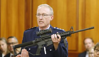 In this April 2, 2019, file photo, police acting superintendent Mike McIlraith shows New Zealand lawmakers an AR-15 style rifle similar to one of the weapons a gunman used to slaughter 51 worshippers at two Christchurch mosques, in Wellington, New Zealand. New Zealand authorities said Saturday, Dec. 21, 2019, their country will be a safer place after gun owners handed in more than 50,000 guns during a buyback program after the government banned assault weapons. But critics say the process was flawed and many owners have illegally stashed their guns. (AP Photo/Nick Perry, File)