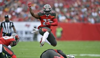Tampa Bay Buccaneers running back Peyton Barber (25) hurdles a teammate on a run against the Houston Texans during the first half of an NFL football game Saturday, Dec. 21, 2019, in Tampa, Fla. (AP Photo/Jason Behnken)  **FILE**