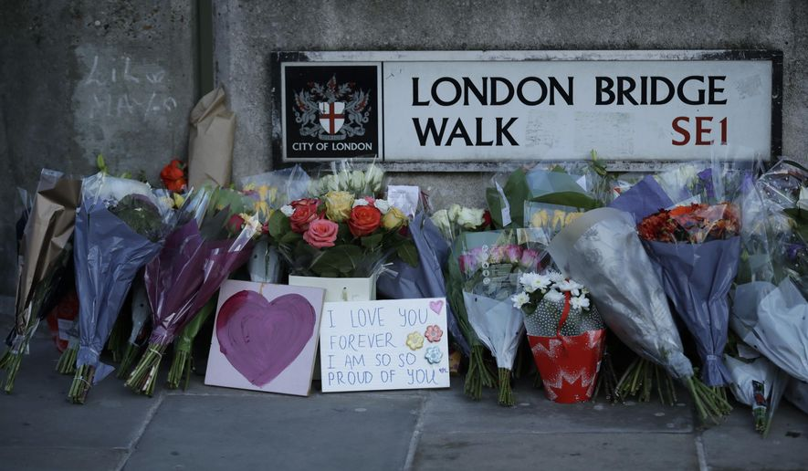 FILE - In this Monday, Dec. 2, 2019 file photo, tributes are placed by the southern end of London Bridge, three days after a man stabbed two people to death and injured three others before being shot dead by police, in London. A mysterious figure who used a rare narwhal tusk to help subdue a knife-wielding extremist on London Bridge last month has been identified as a civil servant in Britain's Justice Ministry. Darryn Frost ended his silence Saturday, Dec. 21 telling Britain's Press Association that he and others reacted instinctively when Usman Khan started stabbing people at a prison rehabilitation program at a hall next to the bridge on Nov. 29.(AP Photo/Matt Dunham, file)