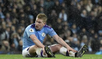Manchester City's Kevin De Bruyne sits on the pitch before being substituted in the last minutes of the English Premier League soccer match between Manchester City and Leicester City at Etihad stadium in Manchester, England, Saturday, Dec. 21, 2019. (AP Photo/Rui Vieira)