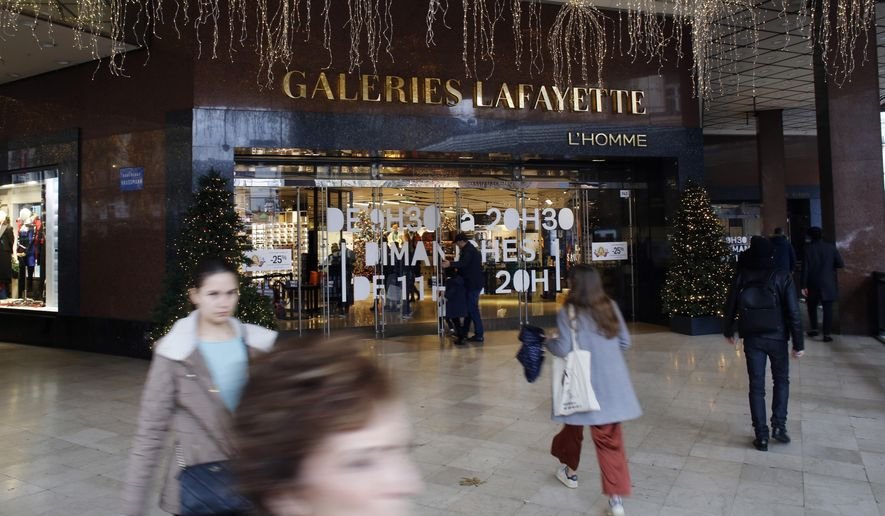 Pedestrians walk in front of the Galeries Lafayette department store in Paris, Thursday, Dec.19, 2019. French retailers, hotels and cafes are struggling at the height of the holiday shopping season, because a protracted transportation strike and repeated protests in Paris and other cities are keeping shoppers and visitors away. And it's the second year in a row _ last year's Christmas season was hit by yellow vest protests. (AP Photo/Thibault Camus)