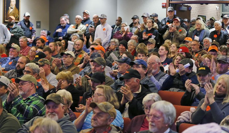 Spectators applaud as the Buckingham County Board of Supervisors unanimously voted to pass a Second Amendment Sanctuary City resolution at a meeting in Buckingham , Va., Monday, Dec. 9, 2019. The board passed the resolution without any public discussion. (AP Photo/Steve Helber)