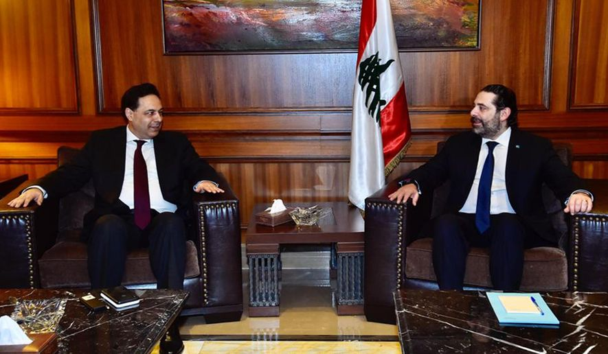 In this photo released by Lebanon's official government photographer Dalati Nohra, newly-assigned Lebanese Prime Minister, Hassan Diab, left, meets with outgoing Prime Minister Saad Hariri, in Beirut, Lebanon, Saturday, Dec. 21, 2019. Diab said he plans to form a government of experts and independents to deal with the country's crippling economic crisis. Diab spoke to reporters Friday, following a meeting with former Prime Minister Saad Hariri, a day after he was asked by the president to form the country's next government. (Dalati Nohra via AP)