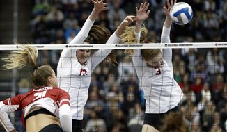 Stanford's Holly Campbell (3) and Audriana Fitzmorris (12) block a spike by Wisconsin's Grace Loberg (21) during the NCAA Division I women's volleyball championship match, Saturday, Dec. 21, 2019, in Pittsburgh. (AP Photo/Keith Srakocic)