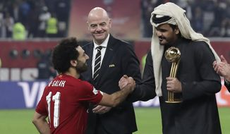FIFA president Gianni Infantino, center, watches as Sheikh Joaan bin Hamad bin Khalifa Al Thani, right, shake hands with Liverpool's Mohamed Salah, left, during the Club World Cup final soccer match between Liverpool and Flamengo at Khalifa International Stadium in Doha, Qatar, Saturday, Dec. 21, 2019. (AP Photo/Hassan Ammar)