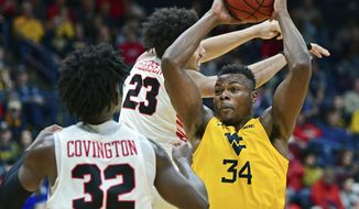 West Virginia forward Oscar Tshiebwe (34) looks to pass while being pressured by Youngstown State forward Olamide Pedersen (23) and guard Garrett Covington (32) during the second half of an NCAA college basketball game, Saturday, Dec. 21, 2019, in Youngstown, Ohio. West Virginia won 75-64. (AP Photo/David Dermer)