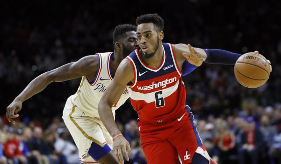 Washington Wizards' Troy Brown Jr., right, tries to dribble past Philadelphia 76ers' James Ennis III during the first half of an NBA basketball game, Saturday, Dec. 21, 2019, in Philadelphia. (AP Photo/Matt Slocum) **FILE**