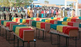 This photo made available from the Mali Army, shows coffins being honored at a funeral ceremony in Gao, Mali, Wednesday, Nov. 20, 2019. The Mali Defense Ministry held a funeral for the 30 soldiers killed in a Monday attack on an army patrol by extremists near the border with Niger. (Mali Army via AP) ** FILE **