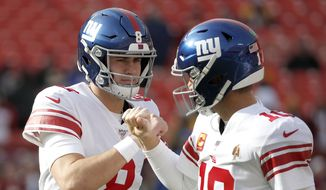 New York Giants quarterback Daniel Jones (8) and quarterback Eli Manning (10) talk while working out prior to an NFL football game against the Washington Redskins, Sunday, Dec. 22, 2019, in Landover, Md. (AP Photo/Alex Brandon) **FILE**
