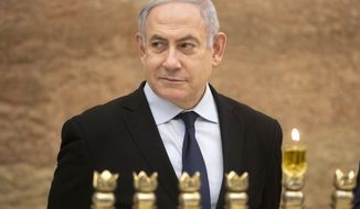 Israeli Prime Minister Benjamin Netanyahu looks on after lighting a Hanukkah candle at the Western Wall, the holiest site where Jews can pray in Jerusalem's old city, Sunday, Dec. 22, 2019. (AP Photo/Sebastian Scheiner)