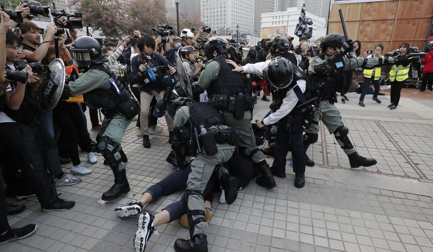 Riot policemen arrest protesters during a rally to show support for Uighurs and their fight for human rights in Hong Kong, Sunday, Dec. 22, 2019. Thousands of demonstrators attended a rally to protest against China's policy about Uighur minority. (AP Photo/Lee Jin-man)