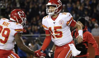 Kansas City Chiefs quarterback Patrick Mahomes (15) celebrates his 12-yard touchdown run with running back Spencer Ware in the first half of an NFL football game against the Chicago Bears in Chicago, Sunday, Dec. 22, 2019. (AP Photo/Nam Y. Huh)