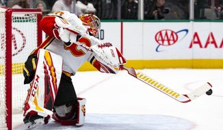 Calgary Flames goaltender David Rittich (33) plays the puck in front of his net during the first period of an NHL hockey game against the Dallas Stars, Sunday, Dec. 22, 2019, in Dallas. (AP Photo/Sam Hodde)