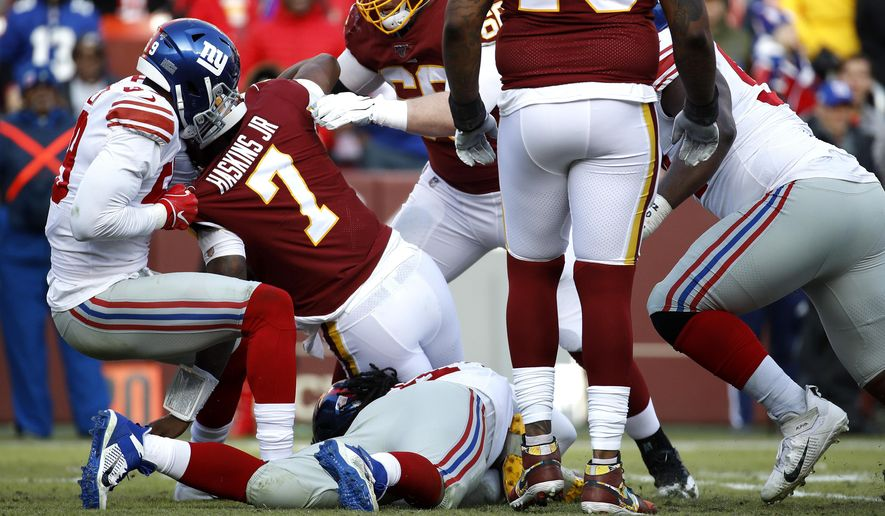 New York Giants linebacker Lorenzo Carter, left, sacks Washington Redskins quarterback Dwayne Haskins (7) during the second half of an NFL football game, Sunday, Dec. 22, 2019, in Landover, Md. Haskins walked to a cart and was taken off the field after the play. (AP Photo/Patrick Semansky)