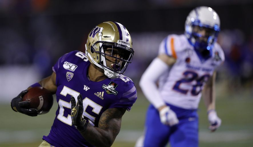 Washington running back Salvon Ahmed (26) carries the ball past Boise State defensive back Kekaula Kaniho (28) during the second half of the Las Vegas Bowl NCAA college football game at Sam Boyd Stadium, Saturday, Dec. 21, 2019, in Las Vegas. (AP Photo/Steve Marcus)