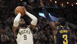 Milwaukee Bucks' Wesley Matthews shoots past Indiana Pacers' Aaron Holiday during the first half of an NBA basketball game Sunday, Dec. 22, 2019, in Milwaukee. (AP Photo/Morry Gash)