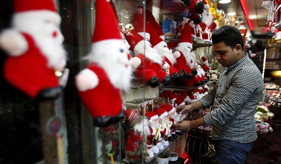 A Palestinian store owner decorates a Santa at his shop in Gaza City, Wednesday, Dec. 18, 2019. (AP Photo/Hatem Moussa)