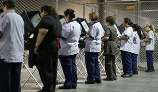 FILE--In this Oct. 26, 2016, file photo, casino workers vote at an early voting site in Las Vegas. Advocates for creating a non-partisan commission to redraw Nevada voting districts instead of the Legislature are offering to amend a proposed statewide ballot initiative to appease a North Las Vegas pastor who has sued to block it. (AP Photo/John Locher, file)