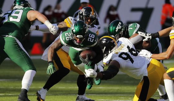 New York Jets running back Le'Veon Bell (26) dives with ball in front of Pittsburgh Steelers defensive tackle Isaiah Buggs (96) during the first half of an NFL football game, Sunday, Dec. 22, 2019, in East Rutherford, N.J. (AP Photo/Seth Wenig)